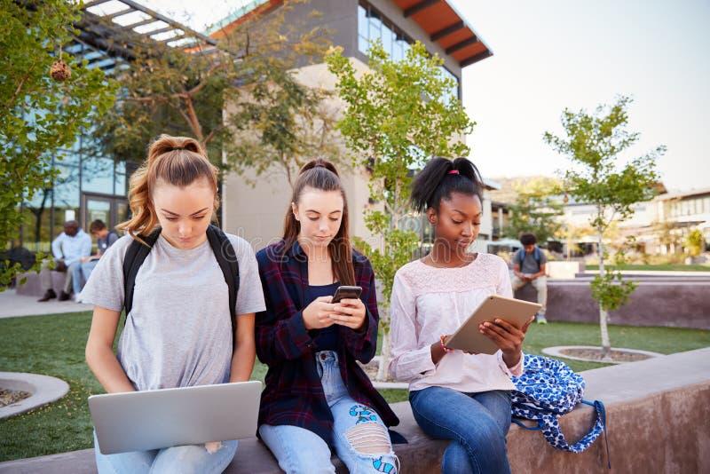 Estudiantes femeninos de la High School secundaria que usan los dispositivos de Digitaces al aire libre durante hendidura imagenes de archivo