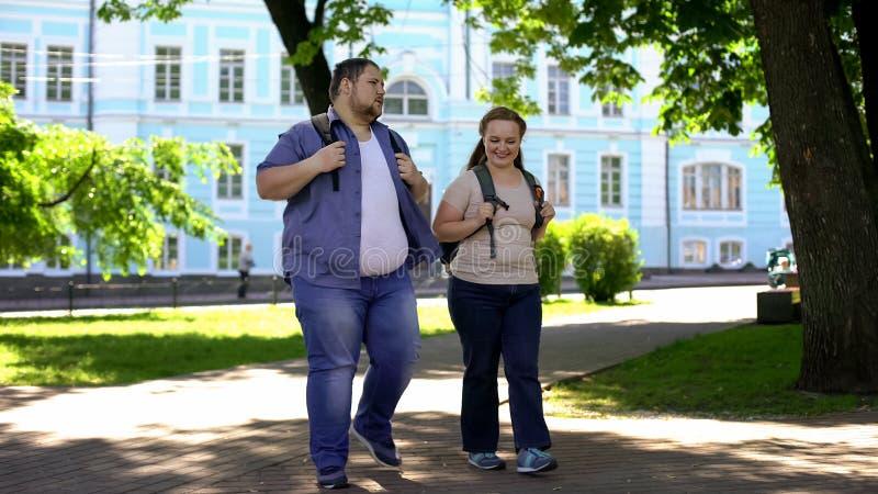 Estudiantes gordos que caminan en parque del campus y que hablan, ligando el fecha, amistad foto de archivo libre de regalías