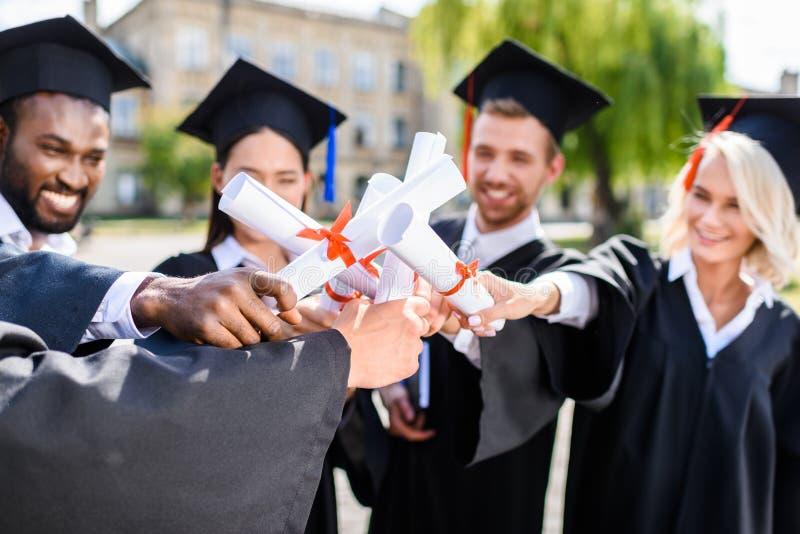 estudiantes graduados jovenes que hacen gesto del equipo fotografía de archivo libre de regalías