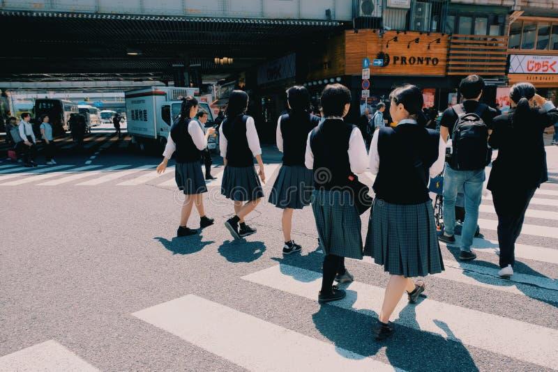 Estudiantes japoneses que caminan a la escuela por la mañana fotos de archivo