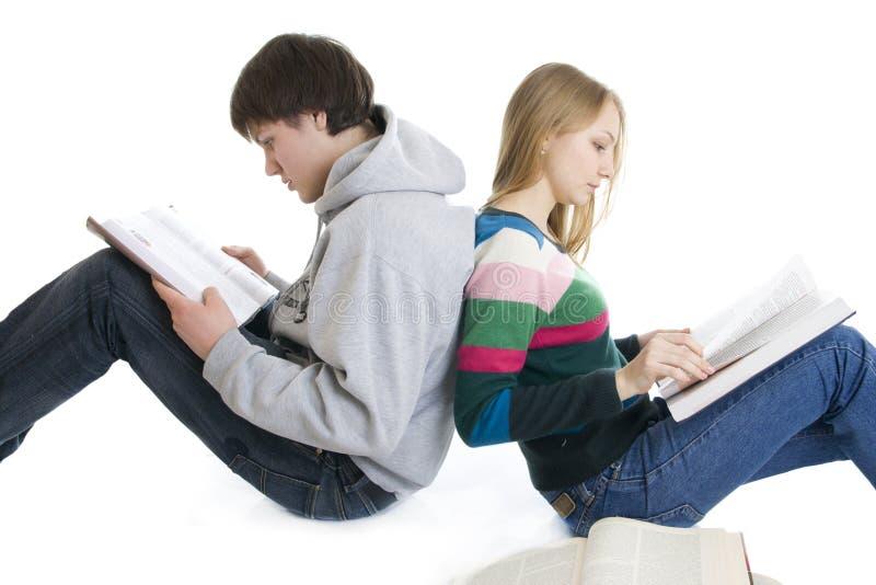 Estudiantes jovenes de los pares con una pila de libros fotografía de archivo