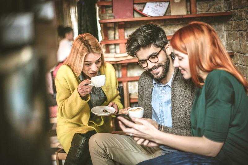 Estudiantes jovenes del árbol en descanso para tomar café imagen de archivo