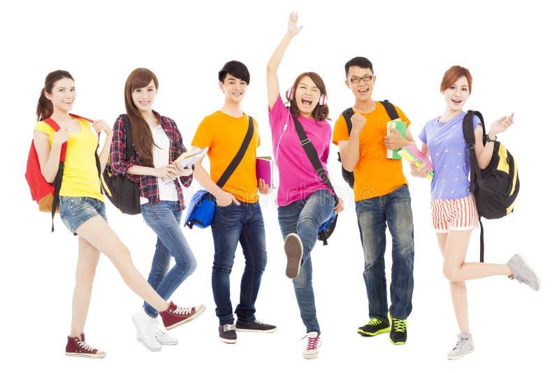 Estudiantes jovenes felices que colocan una fila foto de archivo libre de regalías