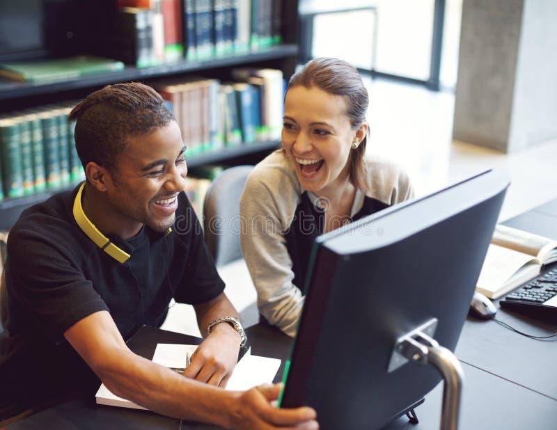 Estudiantes jovenes felices que estudian en una biblioteca moderna fotos de archivo libres de regalías