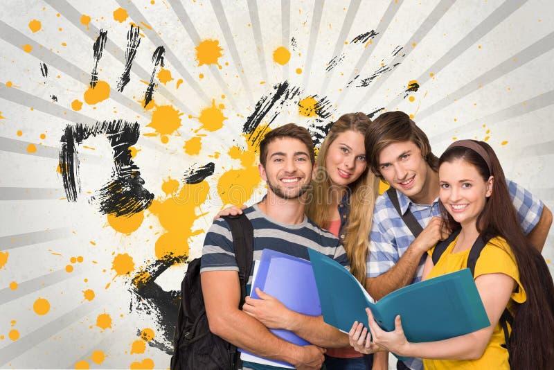 Estudiantes jovenes felices que sostienen carpetas contra fondo salpicado gris, amarillo y negro imágenes de archivo libres de regalías