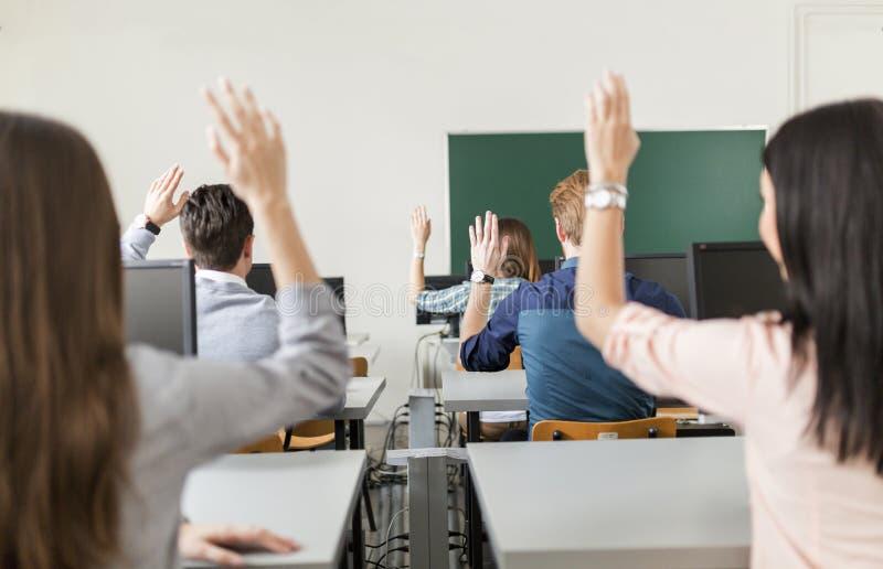 Estudiantes jovenes que aumentan las manos en una sala de clase fotografía de archivo