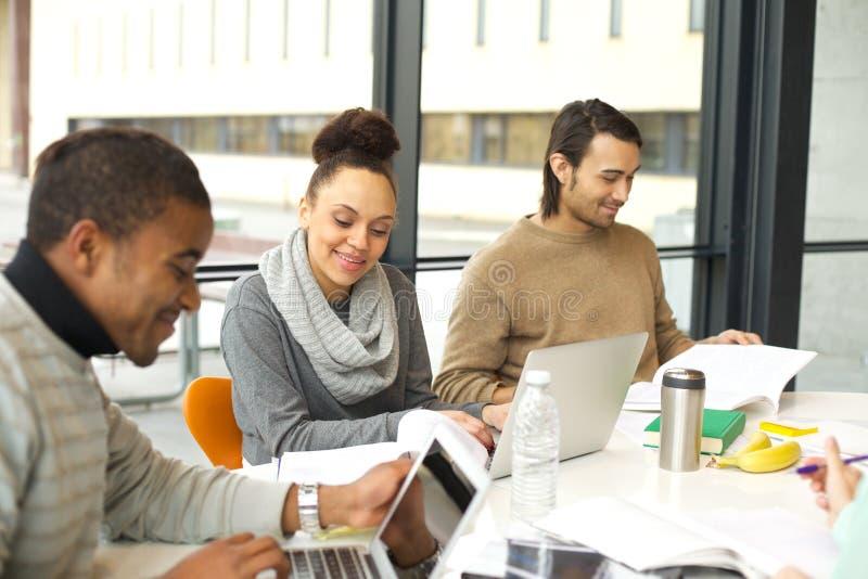 Estudiantes jovenes que estudian en biblioteca de universidad con los libros y el ordenador portátil imagenes de archivo