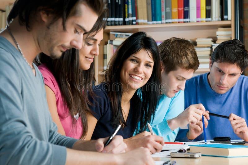 Estudiantes jovenes que estudian en una biblioteca fotografía de archivo