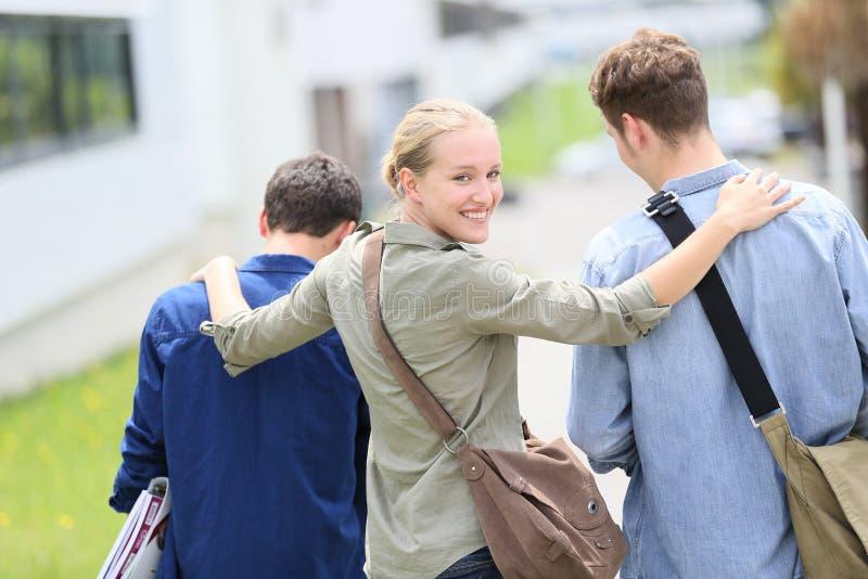 Estudiantes jovenes que salen de campus imagen de archivo