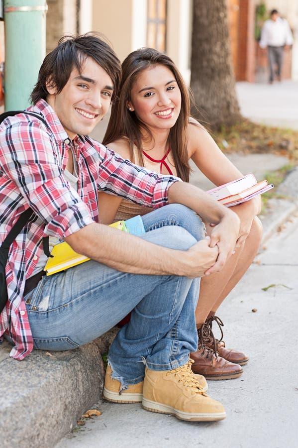 Estudiantes jovenes que se sientan en la calle que sostiene los libros. imagenes de archivo