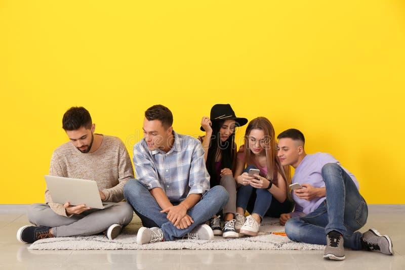 Estudiantes jovenes que se sientan en piso cerca de la pared del color imagen de archivo