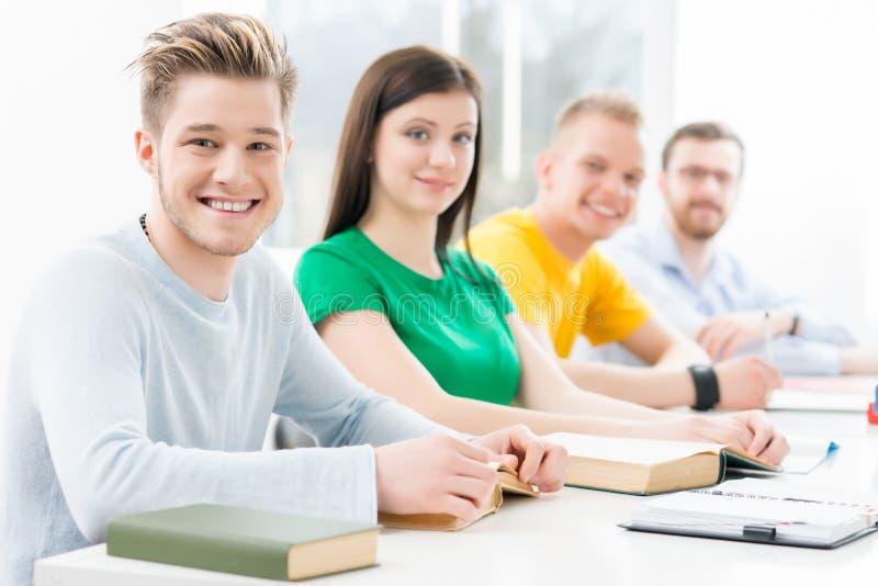 Estudiantes jovenes y elegantes que aprenden en una sala de clase imagen de archivo libre de regalías