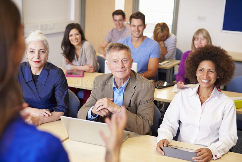 Estudiantes maduros en clase de la enseñanza superior con el profesor foto de archivo libre de regalías