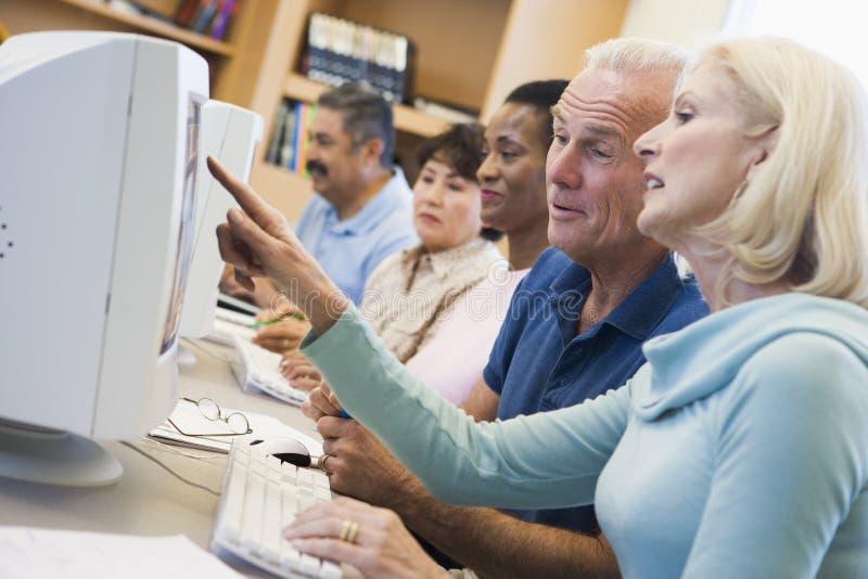 Estudiantes maduros que aprenden destrezas del ordenador imagenes de archivo