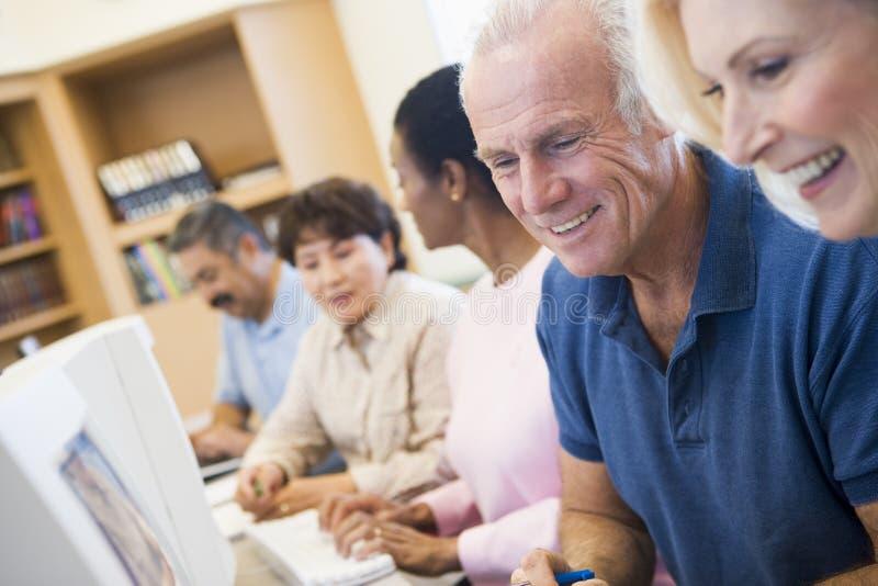 Estudiantes maduros que aprenden destrezas del ordenador imagen de archivo libre de regalías