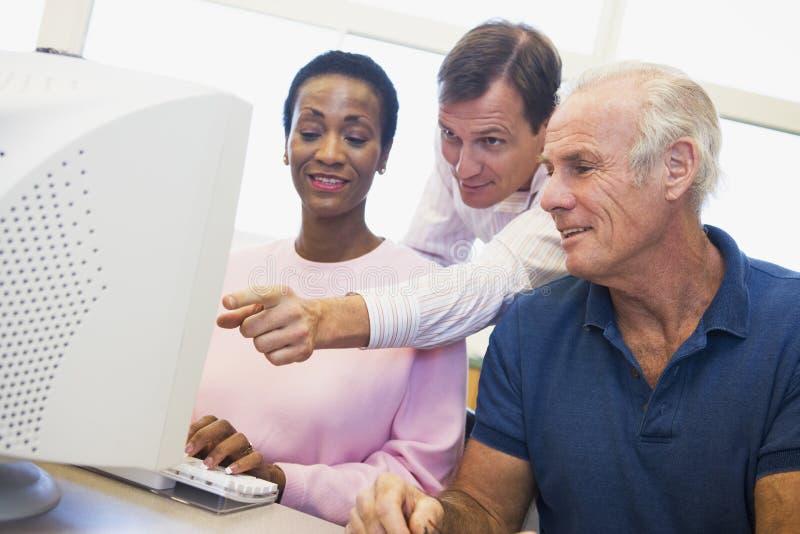 Estudiantes maduros que aprenden destrezas del ordenador foto de archivo