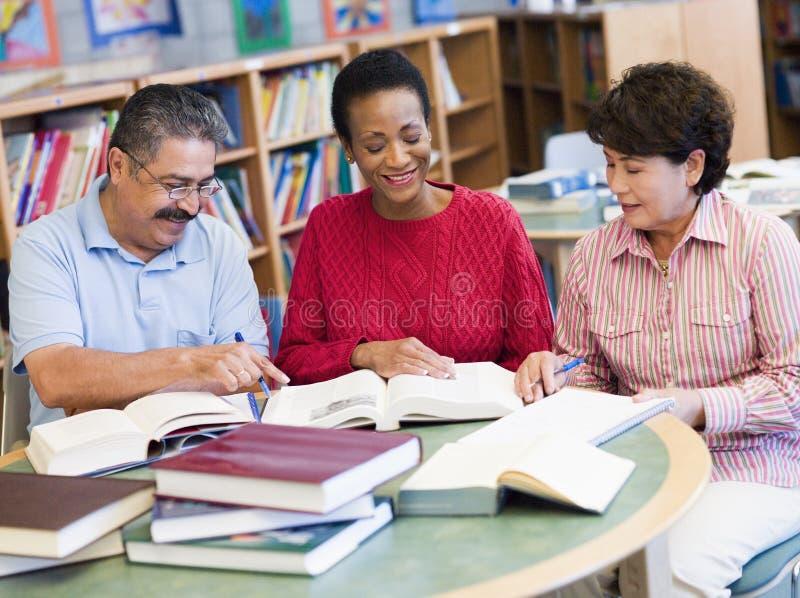 Estudiantes maduros que estudian en biblioteca fotografía de archivo