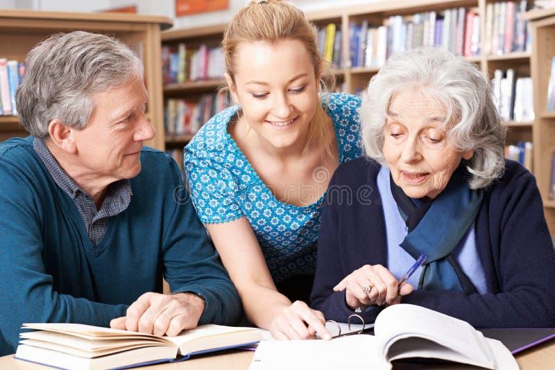 Estudiantes maduros que trabajan con el profesor In Library fotos de archivo