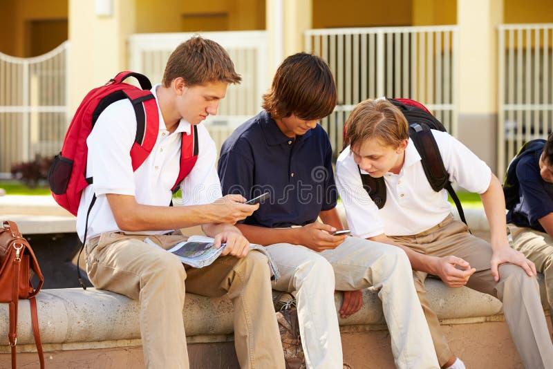 Estudiantes masculinos de la High School secundaria que usan los teléfonos móviles en campus de la escuela imagenes de archivo