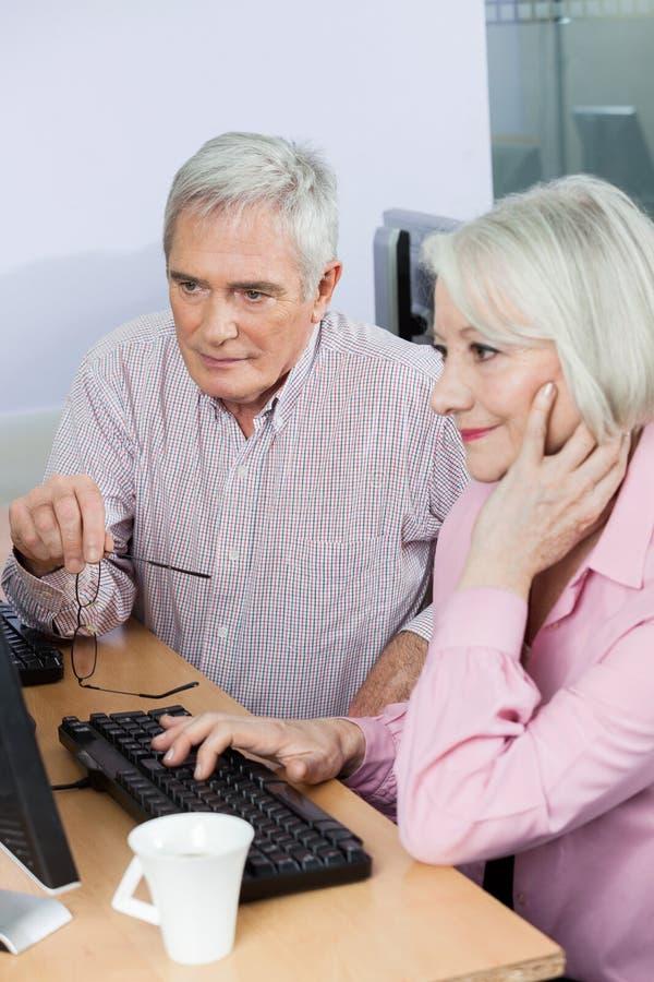 Estudiantes mayores que usan el ordenador junto en sala de clase foto de archivo