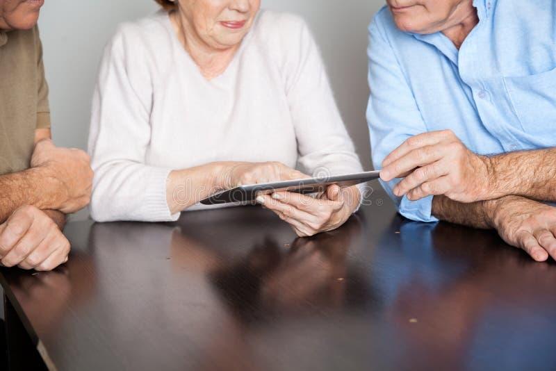Estudiantes mayores que usan la tableta en el escritorio imagenes de archivo