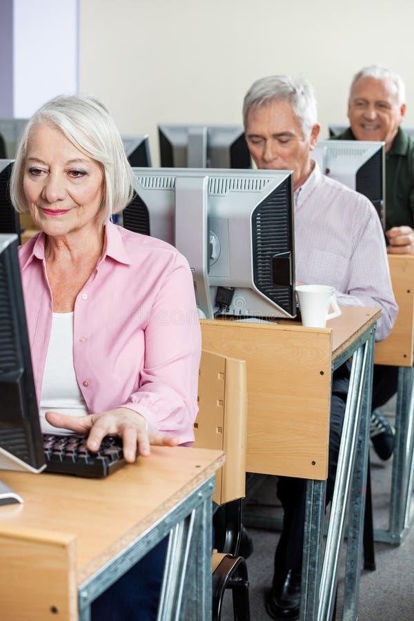 Estudiantes mayores que usan los ordenadores en sala de clase fotos de archivo