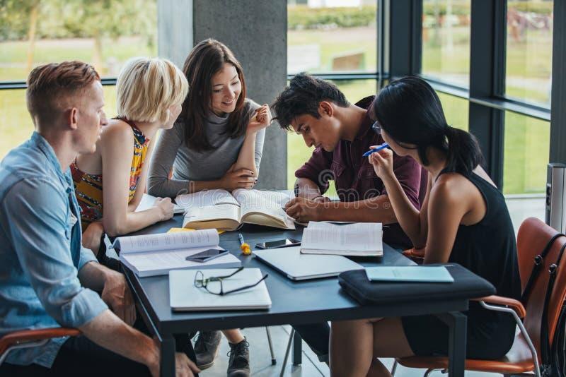 Estudiantes multirraciales que estudian junto en una biblioteca fotos de archivo