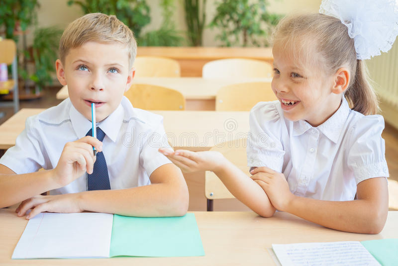 Estudiantes o compañeros de clase en la sala de clase de la escuela que se sienta junto en el escritorio fotos de archivo