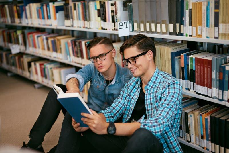 Estudiantes que aprenden el libro de lectura en biblioteca de universidad imagen de archivo libre de regalías