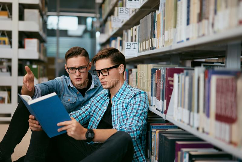 Estudiantes que aprenden el libro de lectura en biblioteca de universidad imagenes de archivo