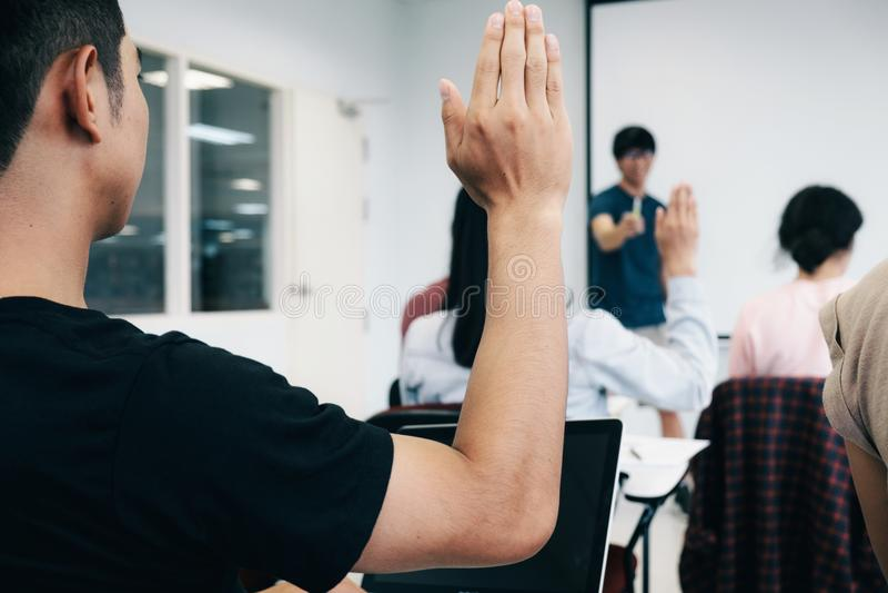 Estudiantes que aumentan las manos en sitio de conferencia de la universidad fotos de archivo libres de regalías