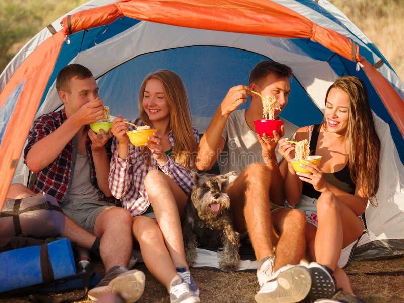 Estudiantes que comen los tallarines cerca de la tienda en un fondo natural Pares en una acampada Viajando y caminando concepto fotos de archivo