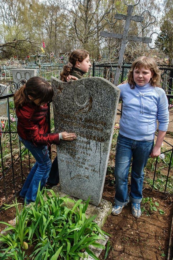 Estudiantes que cuidan para el sepulcro de un director difunto en la región de Kaluga de Rusia fotografía de archivo