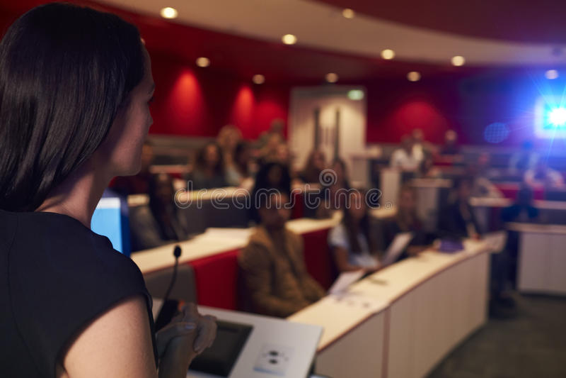Estudiantes que dan una conferencia de la mujer en el teatro de conferencia, primero plano del foco fotografía de archivo libre de regalías