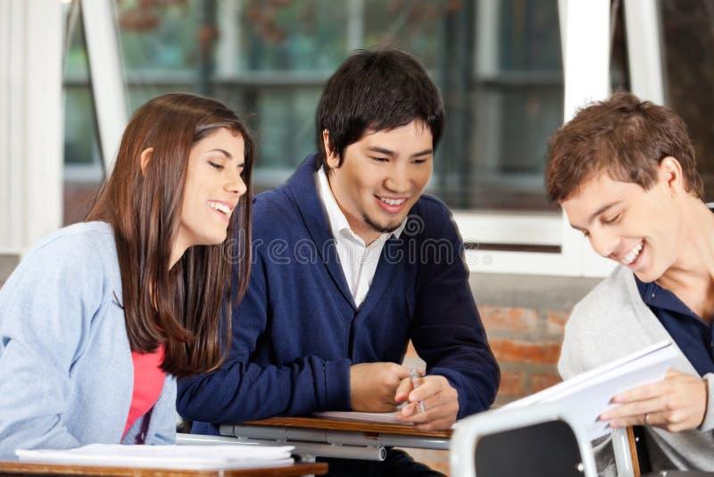 Estudiantes que discuten sobre el libro en sala de clase fotografía de archivo