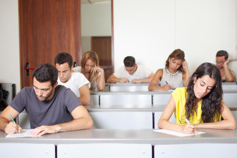 Estudiantes que escriben el examen imagenes de archivo