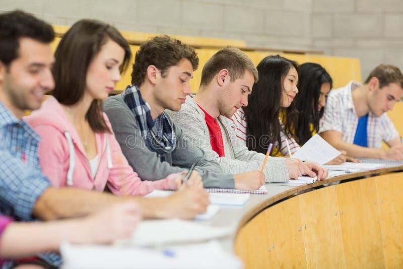 Estudiantes que escriben notas en fila en la sala de conferencias fotos de archivo libres de regalías
