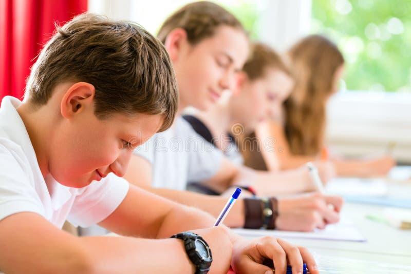 Estudiantes que escriben una prueba en concentrar de la escuela foto de archivo libre de regalías