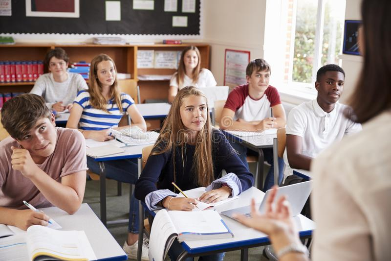 Estudiantes que escuchan el profesor de sexo femenino In Classroom fotos de archivo