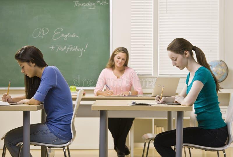 Estudiantes que estudian en sala de clase fotos de archivo