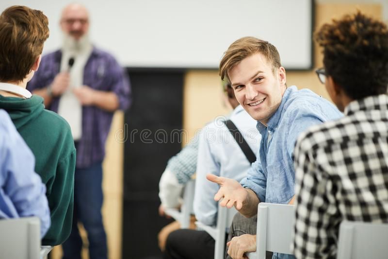 Estudiantes que hablan en auditorio durante conferencia imagenes de archivo