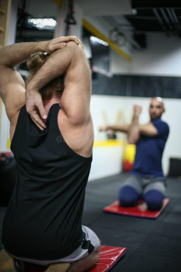 Estudiantes que hacen estirando ejercicio en gimnasio de la escuela imagenes de archivo