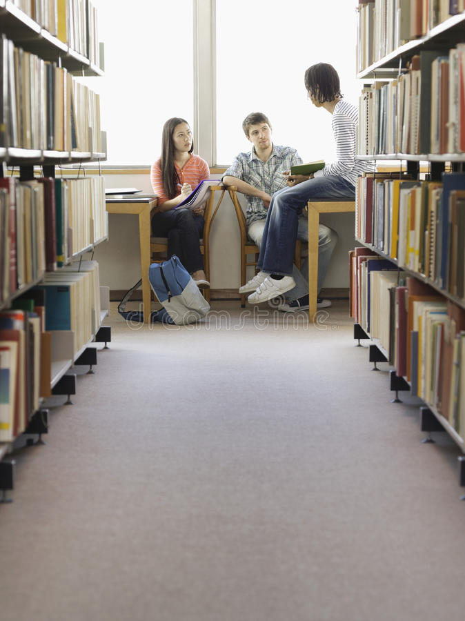 Estudiantes que hacen la preparación en biblioteca foto de archivo libre de regalías