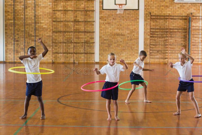 Estudiantes que juegan con el aro del hula en gimnasio de la escuela imagenes de archivo