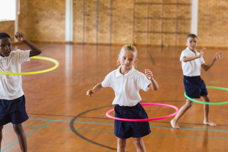 Estudiantes que juegan con el aro del hula en gimnasio de la escuela imagen de archivo