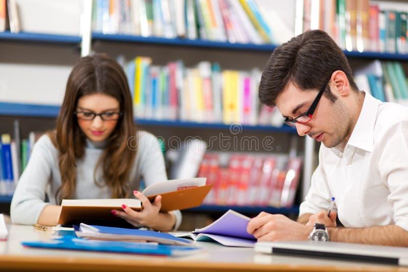 Estudiantes que leen en una biblioteca fotos de archivo libres de regalías