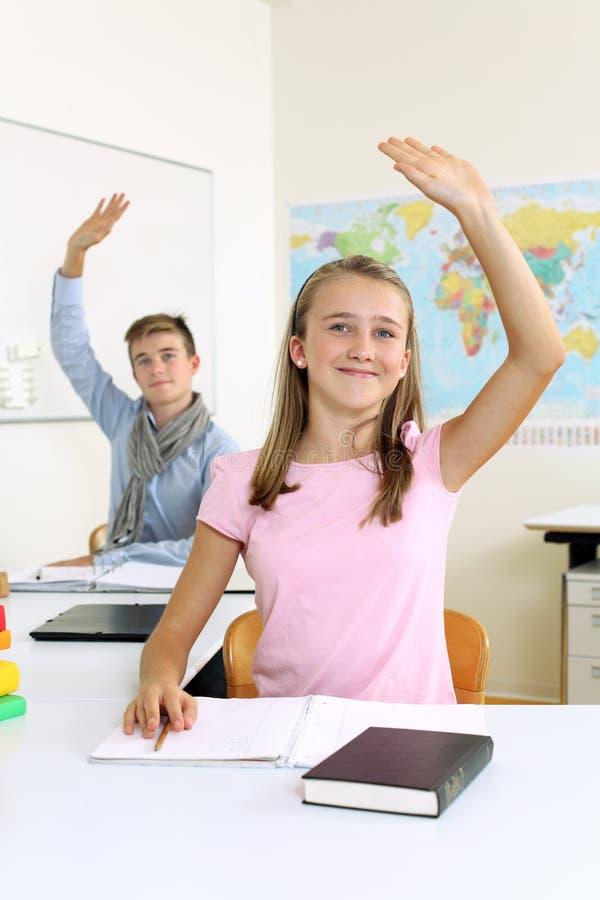 Estudiantes que levantan sus manos en clase imagenes de archivo