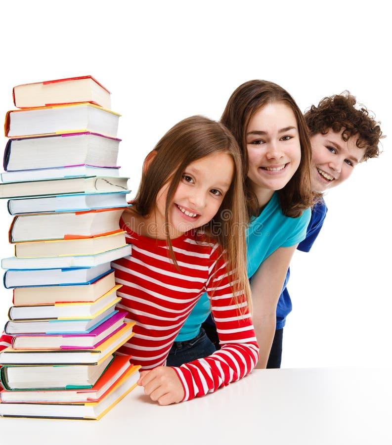 Estudiantes y pila de libros imagenes de archivo