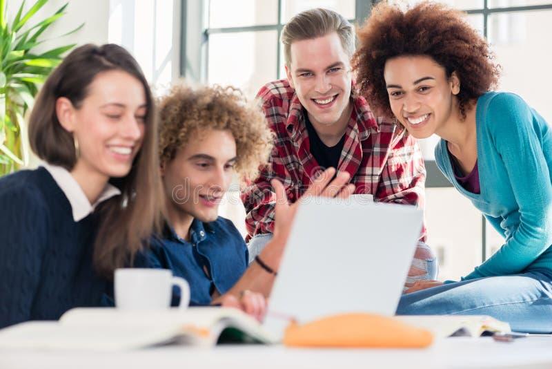 Estudiantes que miran junto un vídeo en línea divertido en un duri del ordenador portátil imagenes de archivo