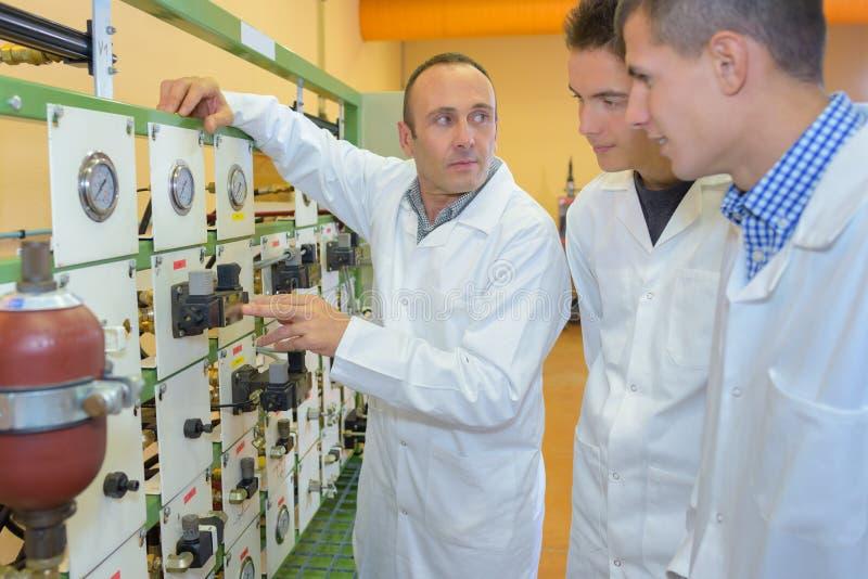 Estudiantes que miran los indicadores técnicos imagen de archivo
